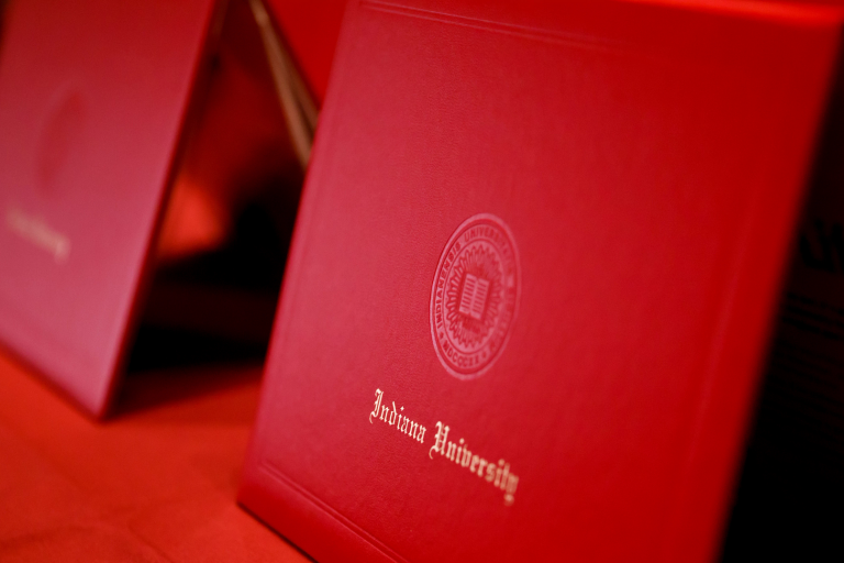 A row of red IU diploma covers