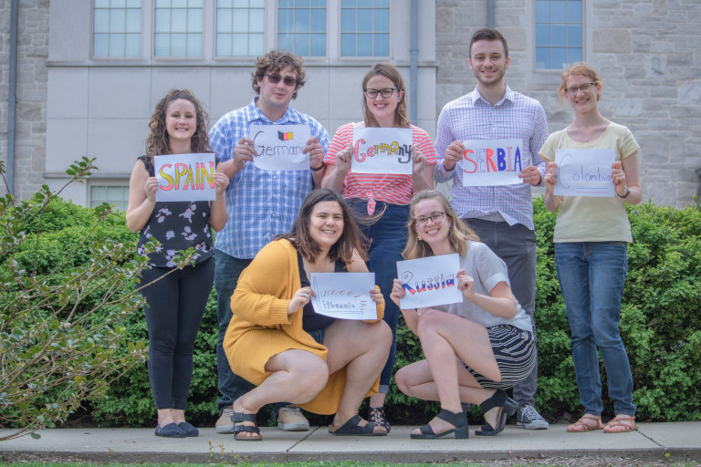Fulbright recipients hold signs that list the country where they'll study
