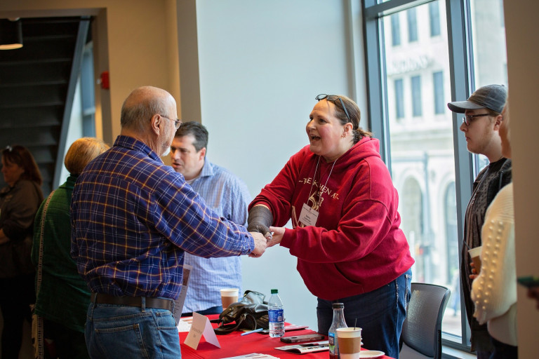 Two attendees of the IU food conference shake hands