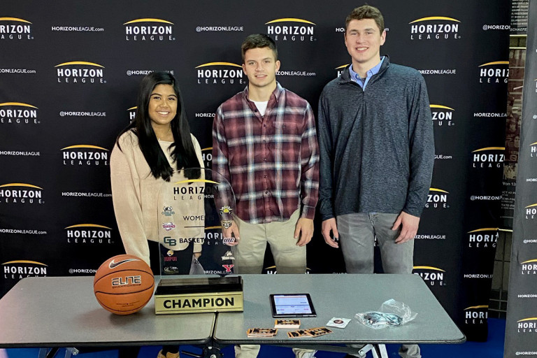 Sports management students stand around a table promoting the Horizon League Tournament