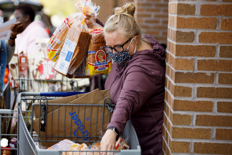 A woman wearing a mask gathers loaves of bread from a grocery cart.
