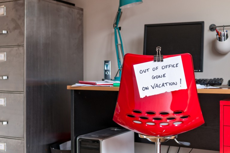 A red chair in an office with a note on it that says 'Out of office, gone on vacation'