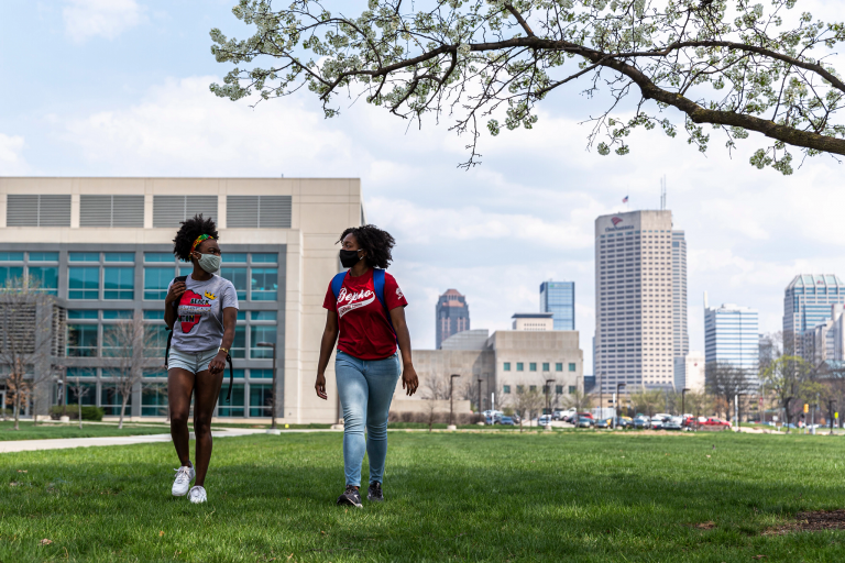Two students in masks walk on the IUPUI campus, with the Indianapolis skyline in the background