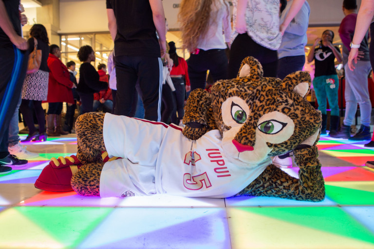 IUPUI mascot Jazzy lies on a multicolored lighted dance floor