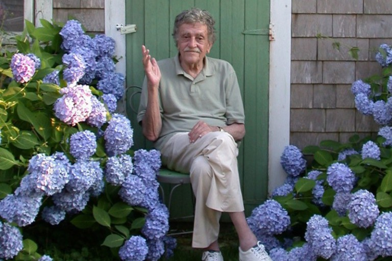 Author Kurt Vonnegut sits outdoors framed by hydrangea flowers