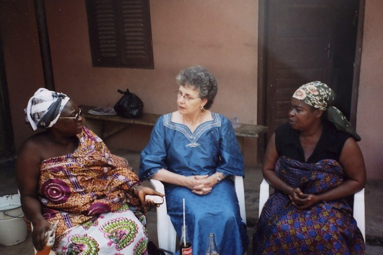 Beverly Stoeltje sits with two women while doing field work in Ghana.