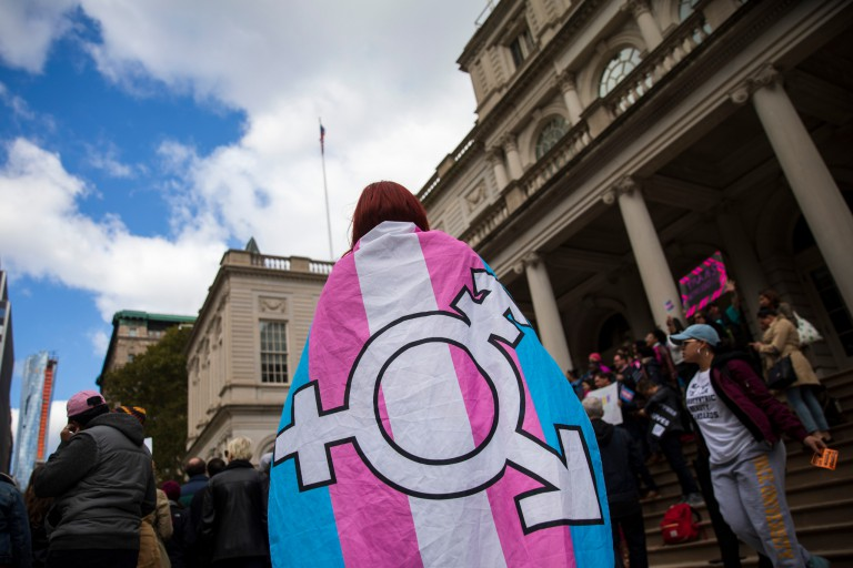 A person with a flag with the transgender symbol wrapped around their neck