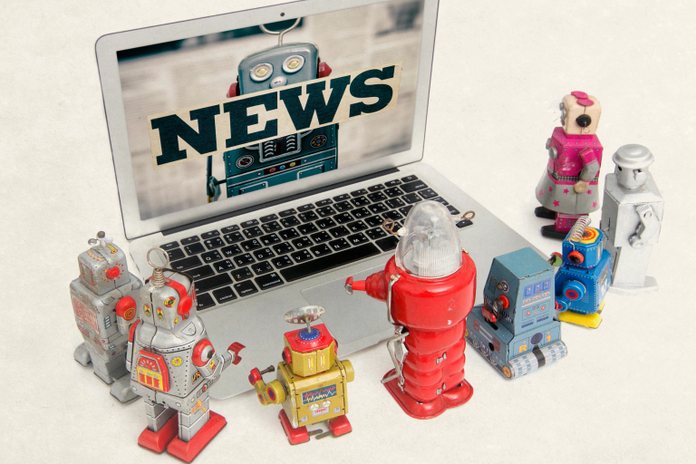 tiny robots look at news on an open laptop screen