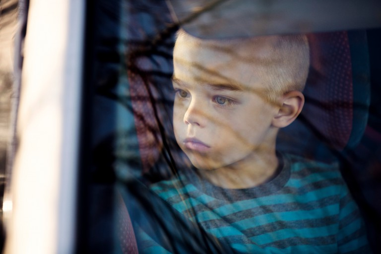 A boy looks out a window.