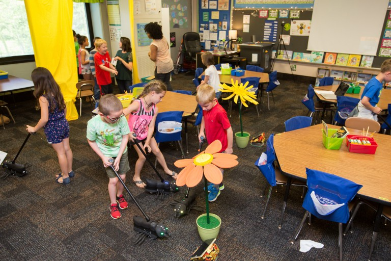 First-grade students play with push toys shaped like ants in a classroom.