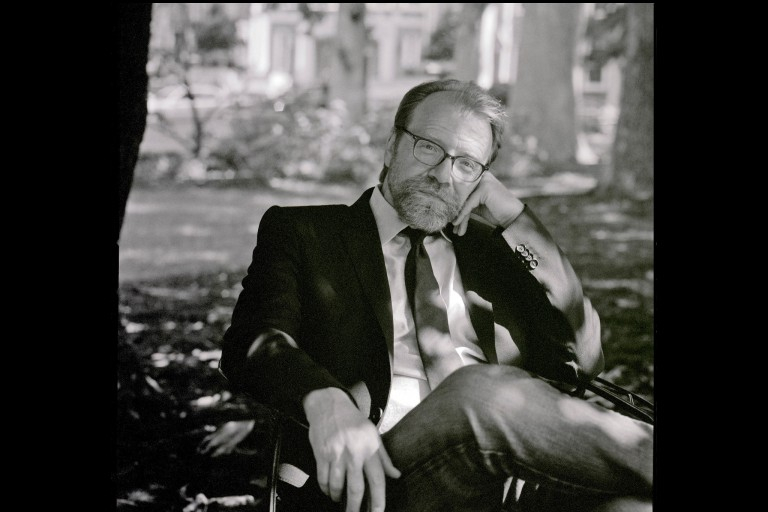 George Saunders sitting outside on a bench