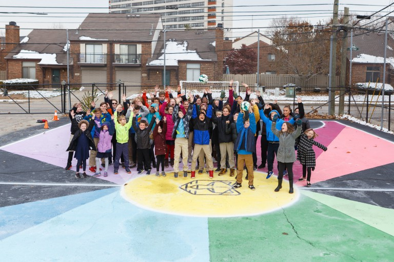 Herron students and Center for Inquiry students pose for a picture on the finished futsal court