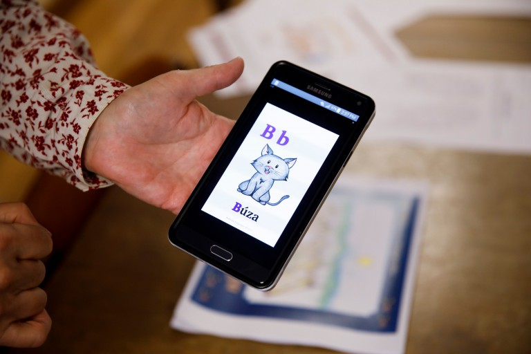 A phone app shows a cartoon cat and its Nakoda translation