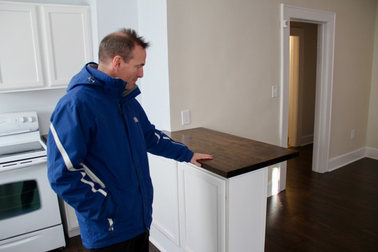 Patrick Monahan examines a kitchen counter in a renovated house.