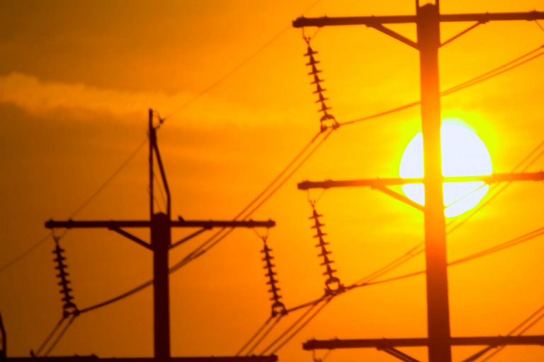 Power lines silhouetted against a bright sun and orange sky
