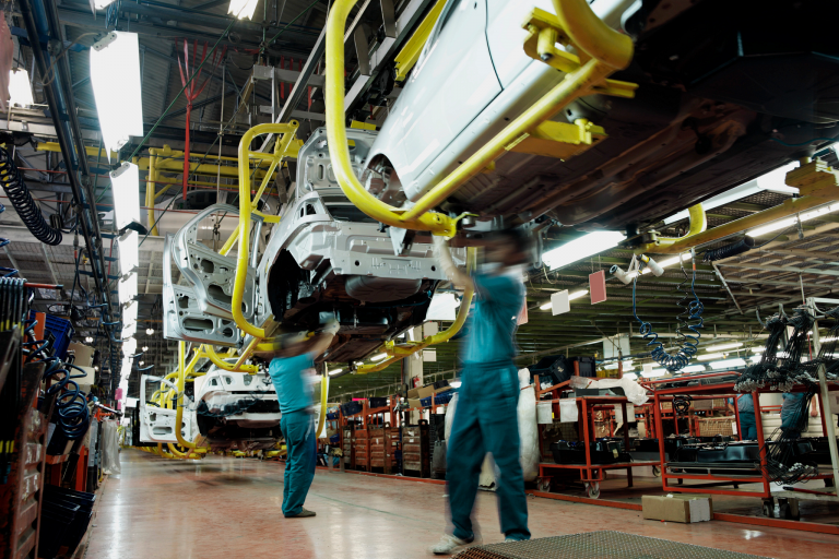 Car manufacturers working on an assembly line