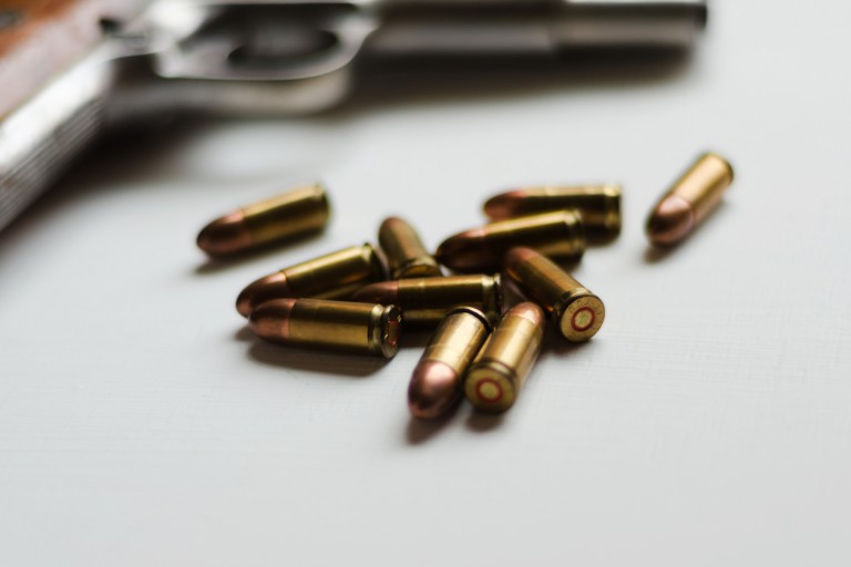 Bullets laying next to a gun