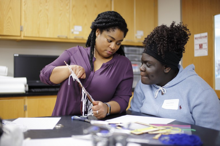 A doctoral candidate helps a high school student with a math weaving activity.