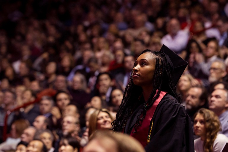 A woman stands among the crowd at graduation.