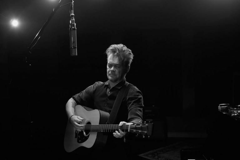John Mellencamp playing guitar and singing