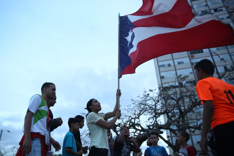 Young people waive the Puerto Rican flag