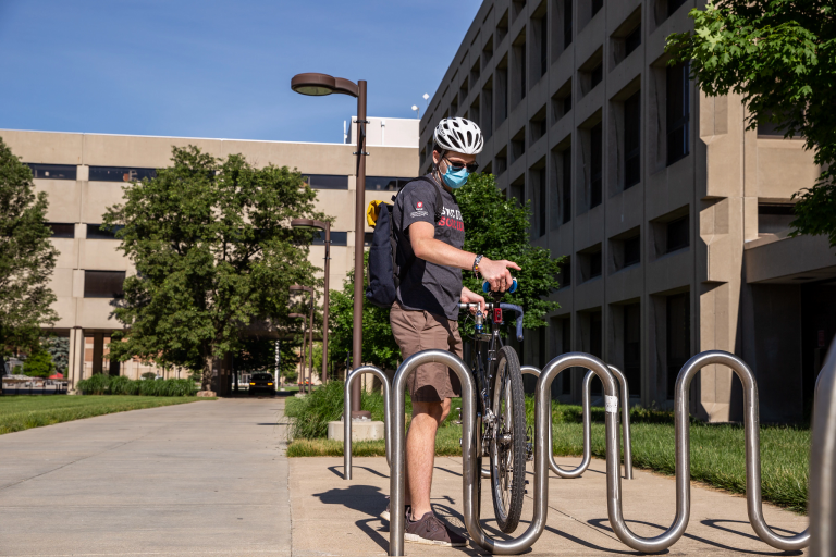 An IUPUI student wears a mask as he parks his bike on the IUPUI campus