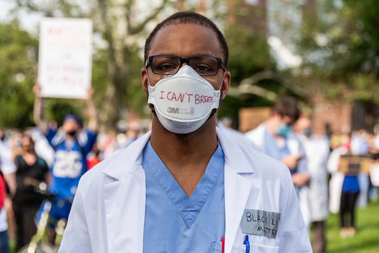 Man in a white coat wears a mask that says 'I can't breathe' on it