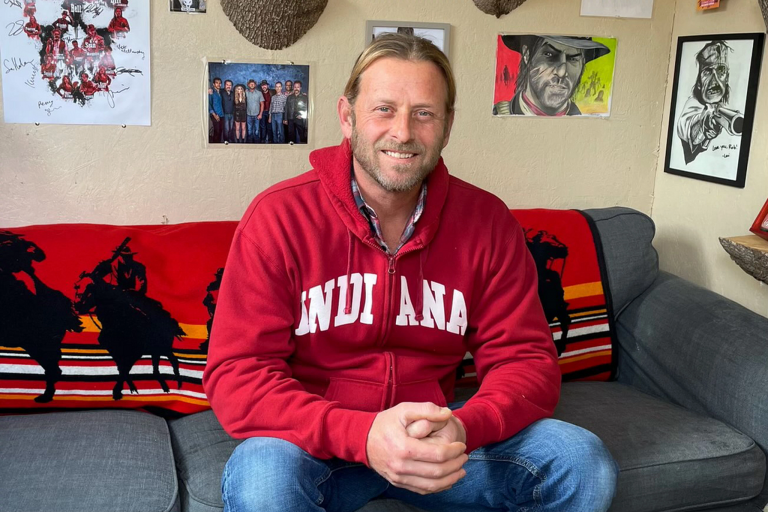 Rob Wiethoff, actor behind John Marston, sits on his couch wearing an IU sweatshirt