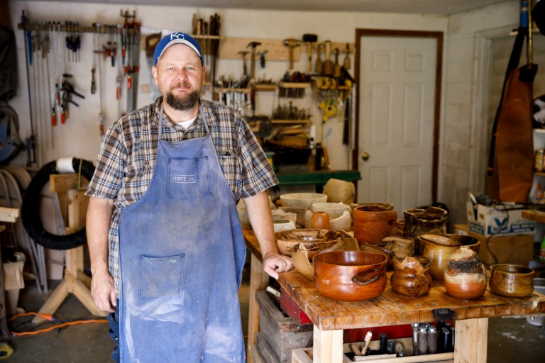 Kevin Jaques stands next to bowls in his workshop