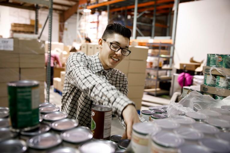 IU freshman Saleem Tucker stocks canned goods at the Hoosier Hills Food Bank