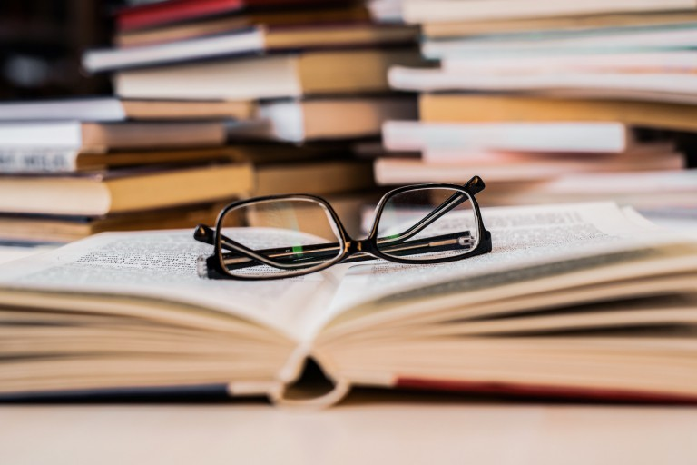 Open book with eyeglasses sitting on top