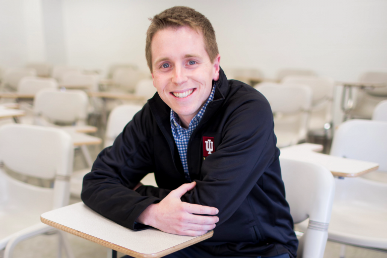 Phil Schuman sits in a classroom