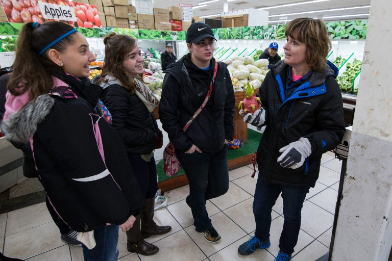 Students learn more about a dragon fruit at a grocery store.