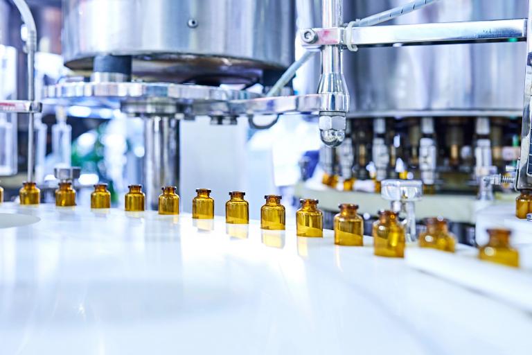 Brown medicine glass bottles on production line.