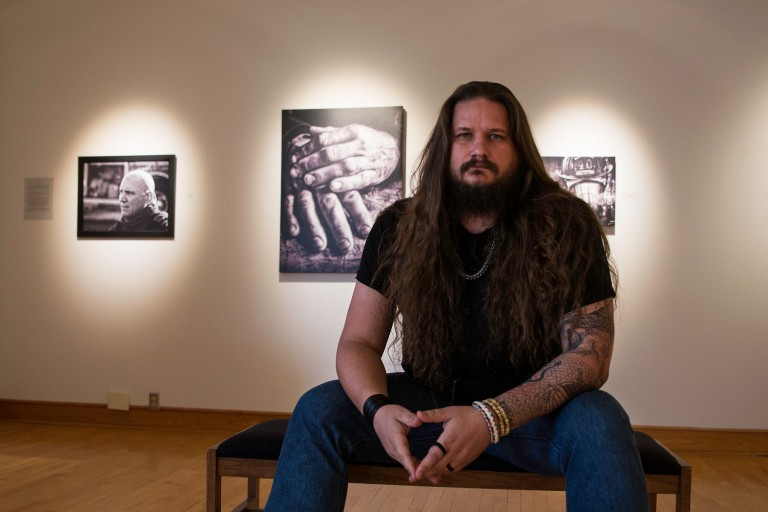 Rob Trlak sitting with some of his photography