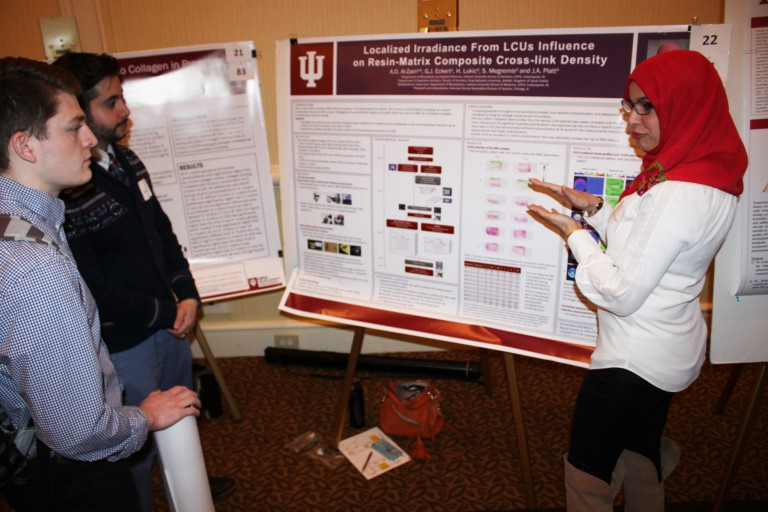 A woman shows off her poster at IUPUI Student Research Day