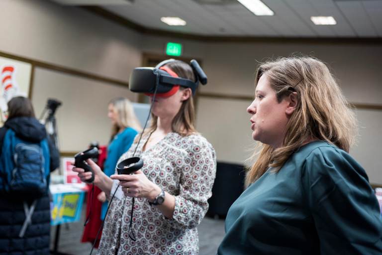 a woman tries on virtual reality goggles