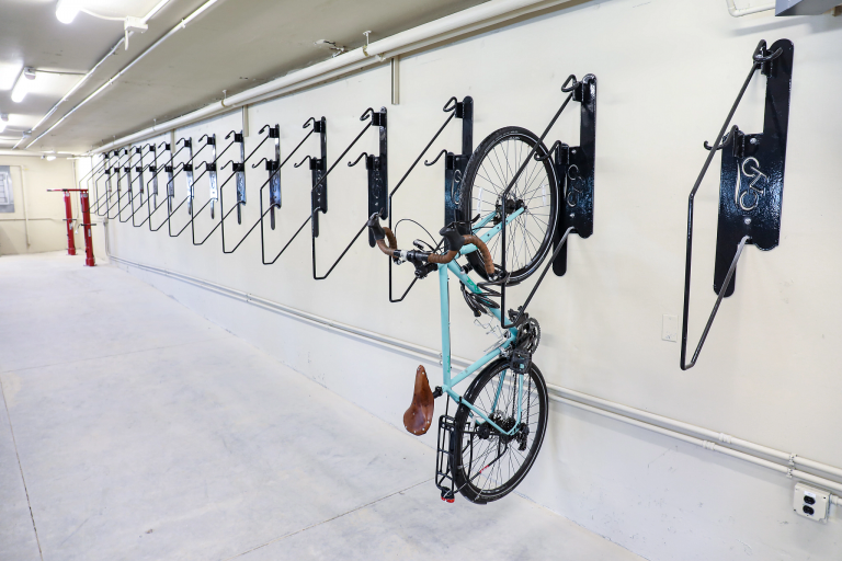 Bike racks and one bicycle mounted vertically on an indoor wall