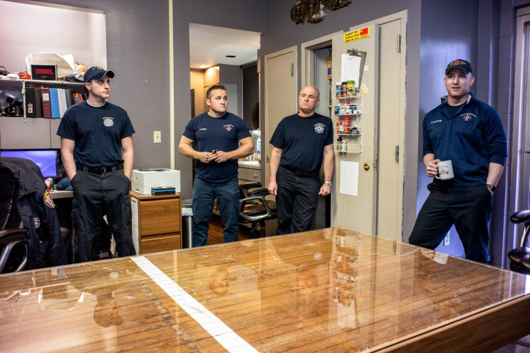 Firefighters stand around their station's new table made from a section of basketball court