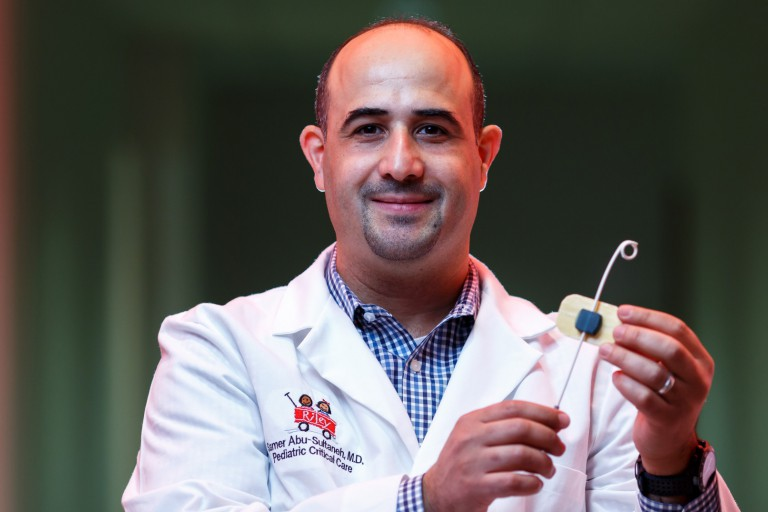 Dr. Samer Abu-Sultaneh holds the chest tube device he developed