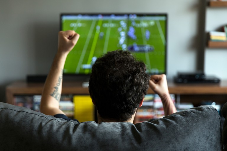 Man on a couch cheering in front of a television with a football game on