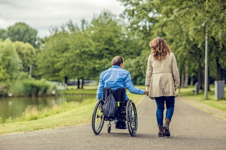 A man in a wheelchair holds hands with a woman who is standing along a tree-lined path in a park