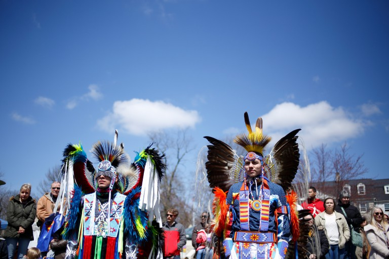 Two men wear traditional Native American attire at IU's powwow