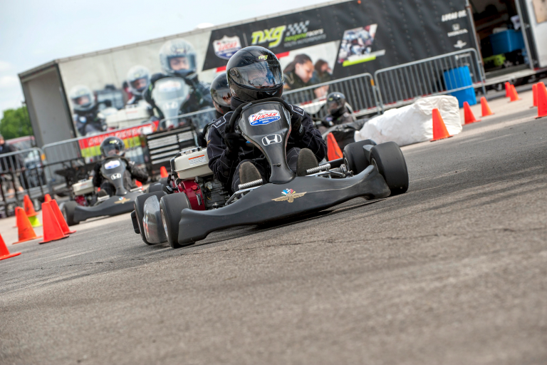 Youth driving a racecar-looking go-cart on a paved track.