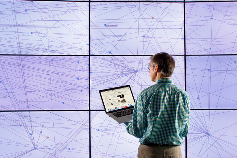 A man holds a laptop in front of a chart displayed on a large monitor