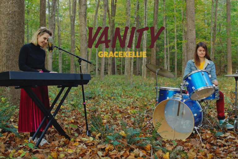 Woman plays keyboard and woman plays drums in woods