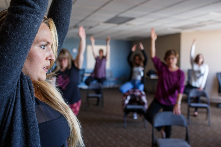 A group of faculty and staff participate in chair yoga on campus.
