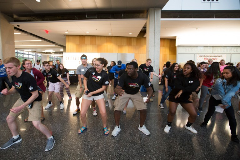 A group of students dance in the Campus Center building.