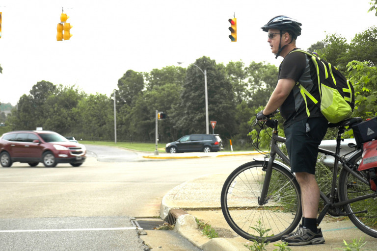 A man riding his bicycle, waiting for a light to change on a curb