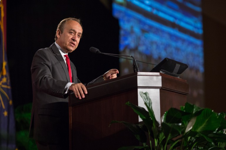 Nasser Paydar stands at a podium as he speaks to an audience about IUPUI